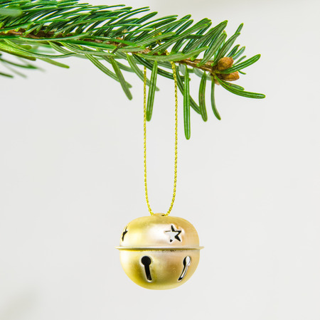 jingle bell: Decorative golden jingle bell ornament in a Christmas tree