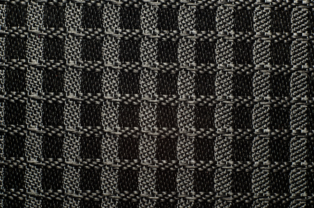 Perforated black textile pattern from audio speaker. Background or backdrop texture.