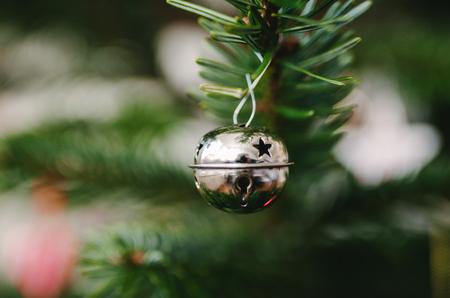 Kerst decoratie ornament op groene kerstboom pijnboom. Wazige achtergrond met bokeh. Stockfoto