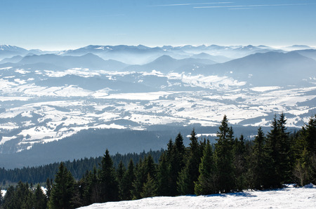 Skiing park Kubinska Hola, Orava, Slovakia. Chair lift and view from the ski slopes on snow covered and foggy valley on the background tatras mountain peaks. Travel destination for winter vacations. Stock Photo