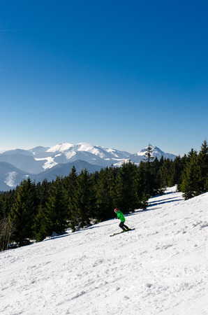 Skiing park Kubinska Hola, Orava, Slovakia. Chair lift and view from the ski slopes on snow covered and foggy valley on the background tatras mountain peaks. Travel destination for winter vacations. Reklamní fotografie
