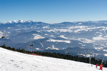 Ski resort Kubinska Hola near Dolny Kubin, Slovakia. Chair lift on the top of ski slope. View of valley. Travel destination for winter vacations. On the background mountains peaks and snow.