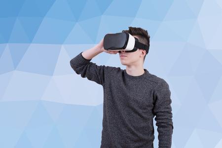 De man met een bril van virtuele realiteit op gekleurde achtergrond. Jonge vent in VR-headset kijkt naar het interactieve scherm. Speel mobiele game app op apparaat. Stockfoto