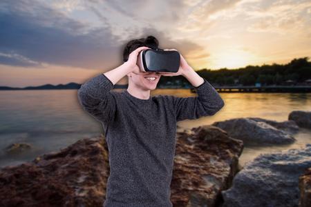 色付きの背景上の仮想現実の眼鏡の男。VR のヘッドセットで若い男は、対話型の画面を見ています。モバイル ゲームのアプリをデバイスで再生。 写真素材