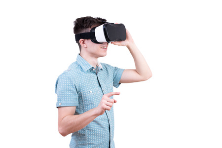hallucinations: Man in blue shirt with glasses of virtual reality on white isolated background. Young guy in VR headset is looking at interactive screen. Playing mobile game app on device. Stock Photo