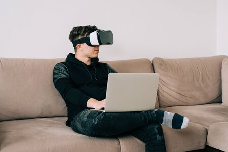 Man in black with glasses of virtual reality on couch. Young guy in VR headset is looking at interactive screen. Playing mobile game app on device. Home office VR. Stock Photo