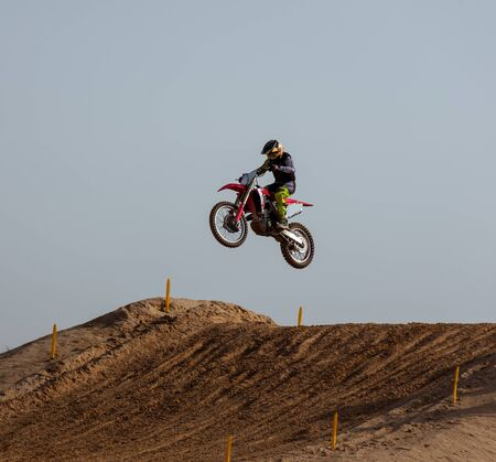 Biker jumping with his motorcycle doing stunt in a motocross racing Stockfoto