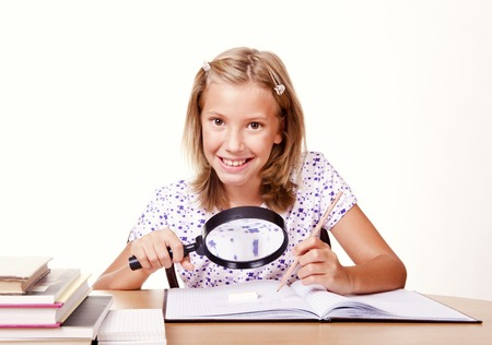 happy young school girl sit with a magnifying glass in hand and write homework photo