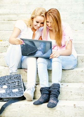 highschool students: happy young highschool students or college girls sitting on the steps outside the school loud laugh and a break from school with a laptop in the hands