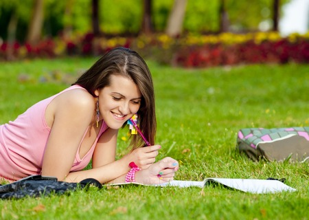 young high school student or college girl lying on the grass in the park and learn