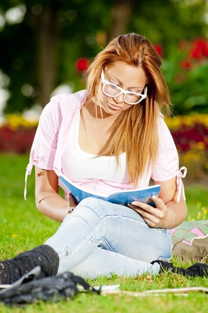 young high school student or college girl learn and sit in the park on the green grass Stock Photo