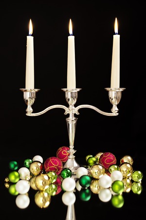 candlestick with three candles, green, gold, pearl and red Christmas tree balls as Christmas and New Year decoration photo