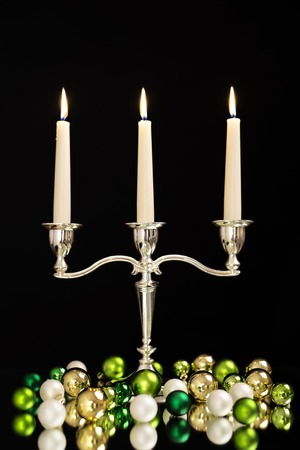 candlestick with three candles, green, gold and pearl Christmas tree balls as Christmas and New Year decoration