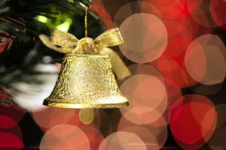 blink: Christmas tree decorated with gold and green bell balls in front of a black background where the yellow lights that blink