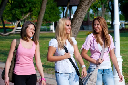 happy young high school students or gollege girls smiling walking to school through the park photo