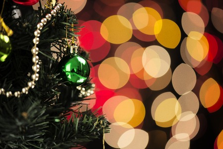 blink: Christmas tree decorated with gold and green ornaments in front of a black background where the red and yellow lights that blink