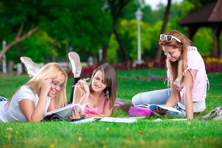 Happy young high school students or college girls learn lying on the grass in the park
