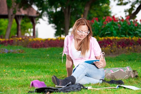 only teenage girls: young high school student or college girl learn and sit in the park on the green grass Stock Photo