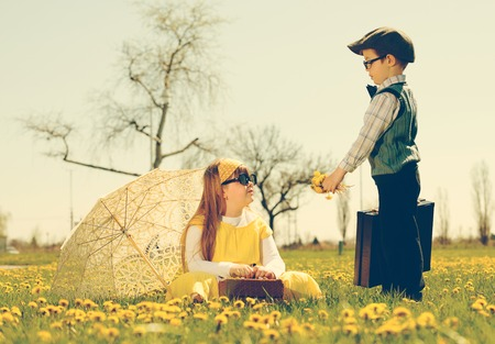 courting: little boy courting a girl of the park in a flower meadow.vintage-look