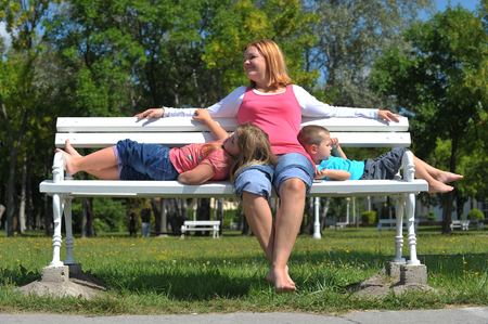 mother on bench: mother with children resting on a bench