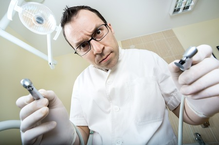 readily: young dentist with sterile mask readily approaching a patient with dental instruments held in the hands protected with surgical gloves Stock Photo