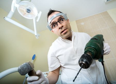 crazy dentist ready to drill approached the patient and dental instruments keeping the hands that protected surgical gloves Reklamní fotografie