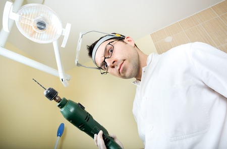 approached: crazy dentist ready to drill approached the patient and dental instruments keeping the hands that protected surgical gloves Stock Photo