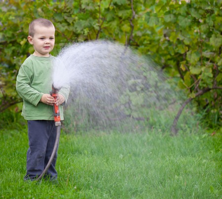 boy watering the grass