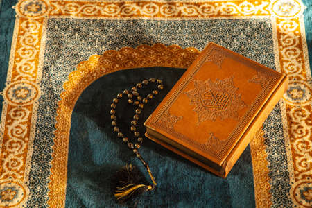 Rosary and Noble Quran on Praying Carpet with Natural Light