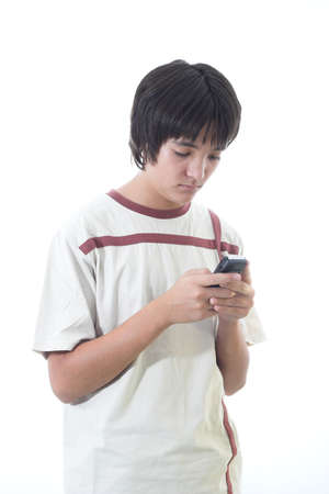 A boy is sending or watching SMS or playing with mobile phone. photo