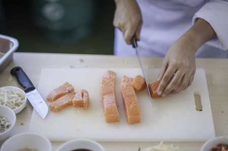 mea: seafood chef slicing salmon fish Editorial