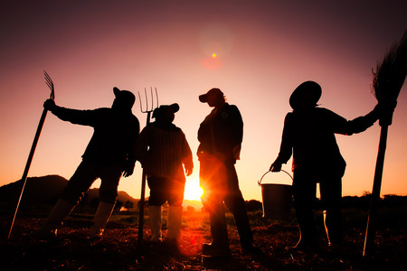 Silhouette, farmers holding pitchfork in sunset Фото со стока - 92539027