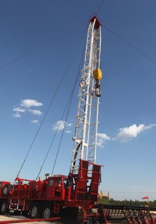 sucker: Oil Field Pulling Unit installing new sucker rods in an oil well Stock Photo