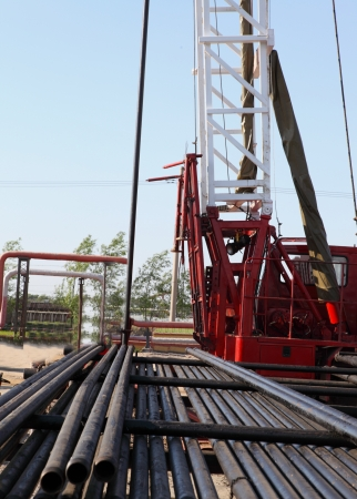 boring rig: Oil Field Pulling Unit installing new sucker rods in an oil well Stock Photo