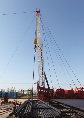Oil Field Pulling Unit installing new sucker rods in an oil well photo