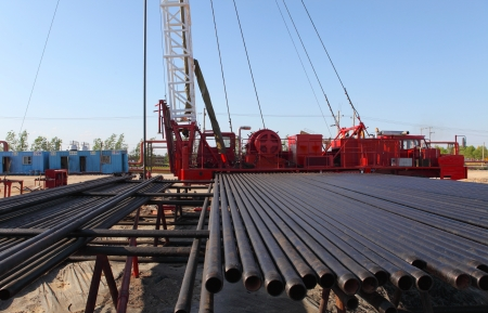oilwell: Oil Field Pulling Unit installing new sucker rods in an oil well Stock Photo