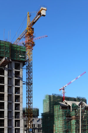 Building crane and building under construction against blue sky  photo