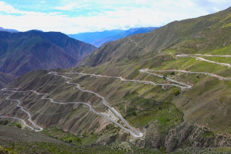 The long curving montanic road in Tibetan plateau summer, China