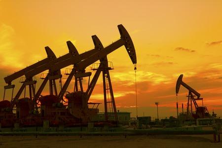 huile: Pompe � huile sur orange coucher de soleil �ditoriale