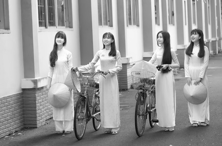conical hat: Ho Chi Minh City, Vietnam - September 13rd, 2015: Group teenager girls in long dress is leading a bicycle to go to school with  smiling face in the morning at school Quang Trung, city Ho Chi Minh City, Vietnam Editorial