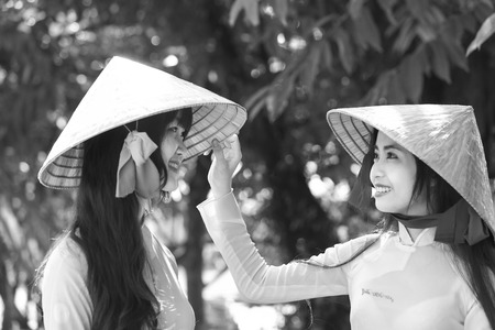 endearing: Ho Chi Minh City, Vietnam - September 13rd, 2015: Students help your friend conical hats  to school endearing expression of friendship kidney morning at school Quang Trung, Ho Chi Minh City, Vietnam