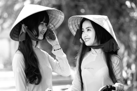 vietnamese ethnicity: Ho Chi Minh City, Vietnam - September 13rd, 2015: A girl student was watching her friend with a smile and beautiful bright eyes showing innocent beauty of students in Ho Chi Minh, Vietnam