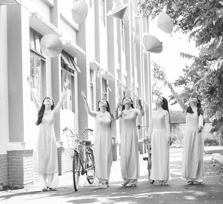 Ho Chi Minh, Vietnam - 13o de septiembre de 2015: Grupo muchachas del estudiante están jugando con rebote alto sombrero cónico crear belleza inocente, inocente patio de la escuela del partido por la mañana en Ho Chi Minh, Vietnam