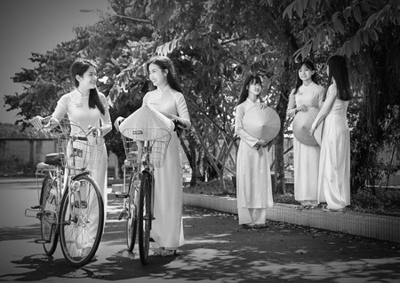 academic dress: Ho Chi Minh City, Vietnam - September 13rd, 2015: Group student girls are chatting academic exchange with the white long dress and hat beautiful leaf corner schoolyard in the morning at school in Ho Chi Minh City, Vietnam Editorial