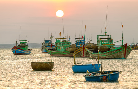 Binh Thuan, Vietnam - March 20th, 2015: Sunset on sea with boats boats pannier big lead out to see the sun very big was going out all over the sky yellow make more nicer waters in Binh Thuan, Vietnam