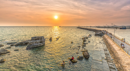 Phu Quoc, Vietnam - April 10th, 2015: Beauty sunset on the shore breakwater path that the sun was going out, below are the fishing boats make more vivid sunsets, to attract tourists tourism in Phu Quoc, Vietnam