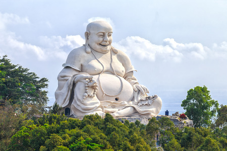buddha face: An Giang, Vietnam - April 12th, 2015: Architectural Specification biggest Maitreya Buddha merciful smile, bright white amnesty on high peaks attracts many Buddhists to pray for peace. This is the beautiful architecture of Buddha in An Giang, Vietnam