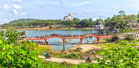 scheduled: An Giang, Vietnam - April 12th, 2015: Panorama Maitreya Buddha bridge crossing big lake, surrounded temples including huge worshiped spiritual place attract tourists scheduled visit in An Giang, Vietnam
