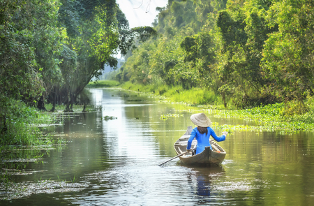 Dong Thap, Vietnam - January 14th, 2014: Woman rowing on the river and passed the house homeland with small body, shirt Ba Ba and conical hats typical of Southeast women in a spring afternoon in Dong Thap, Vietnam