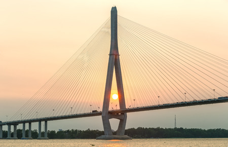 can tho: Can Tho, Vietnam - April 4th, 2015: close up of cable stayed bridge at sunset with the sun in the abutment shown brilliant achievements of human development in the Mekong Delta in Can Tho, Vietnam